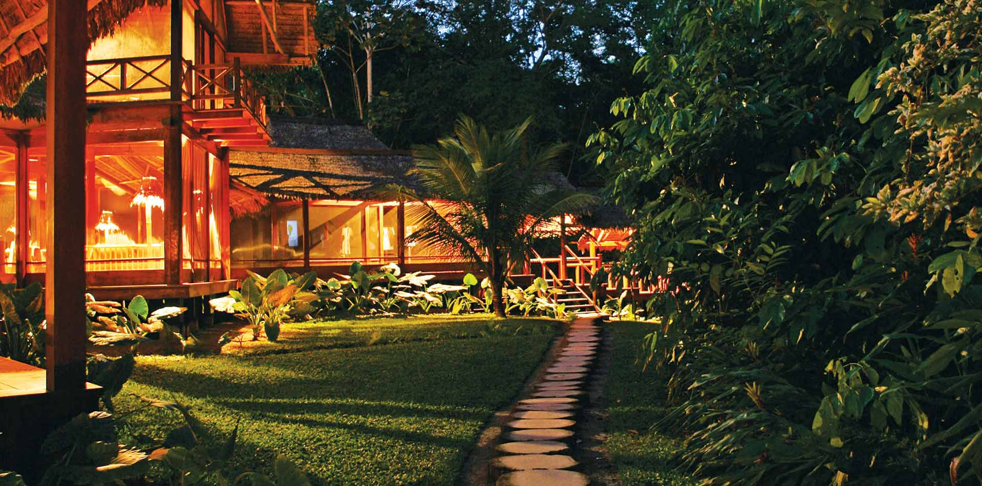 South America Peru Inkaterra Reserva Amazonica eco-lodge hotel exterior at night - luxury vacation destinations