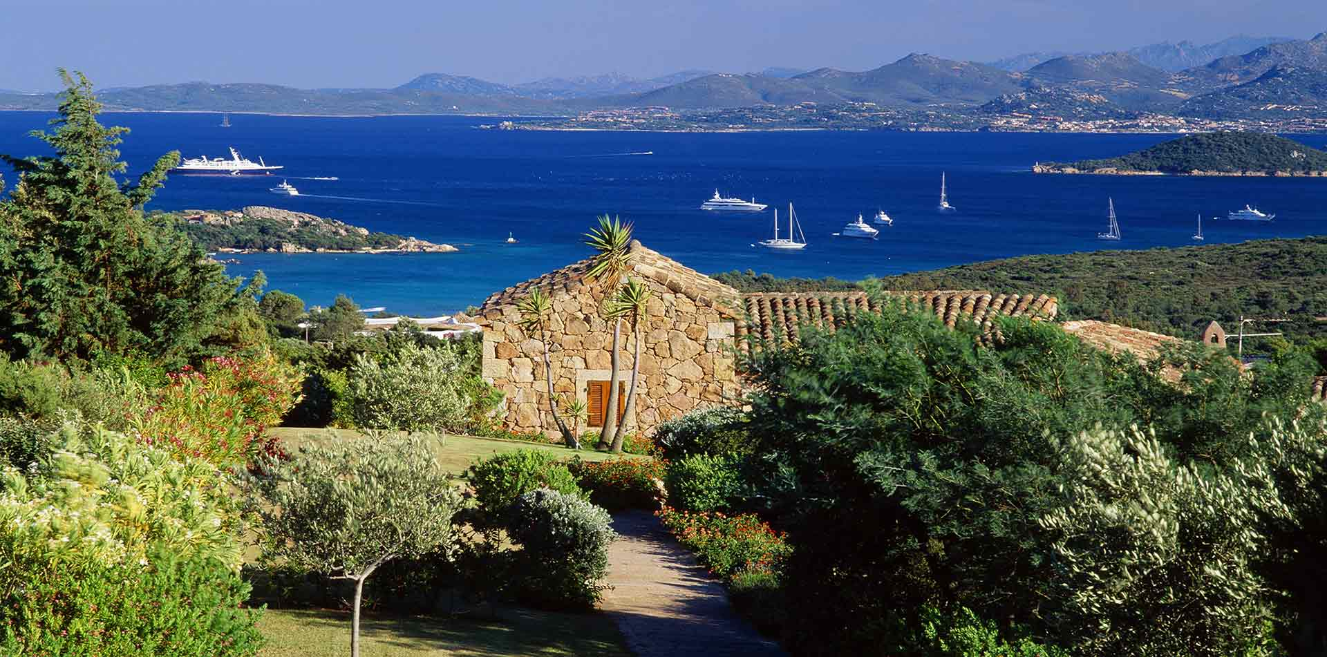 Europe Italy Sardinia rustic villa overlooking the harbor with sailboats and yachts - luxury vacation destinations