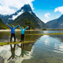 Oceania New Zealand South Island couple standing in front of mountains in Milford Sound- luxury vacation destinations