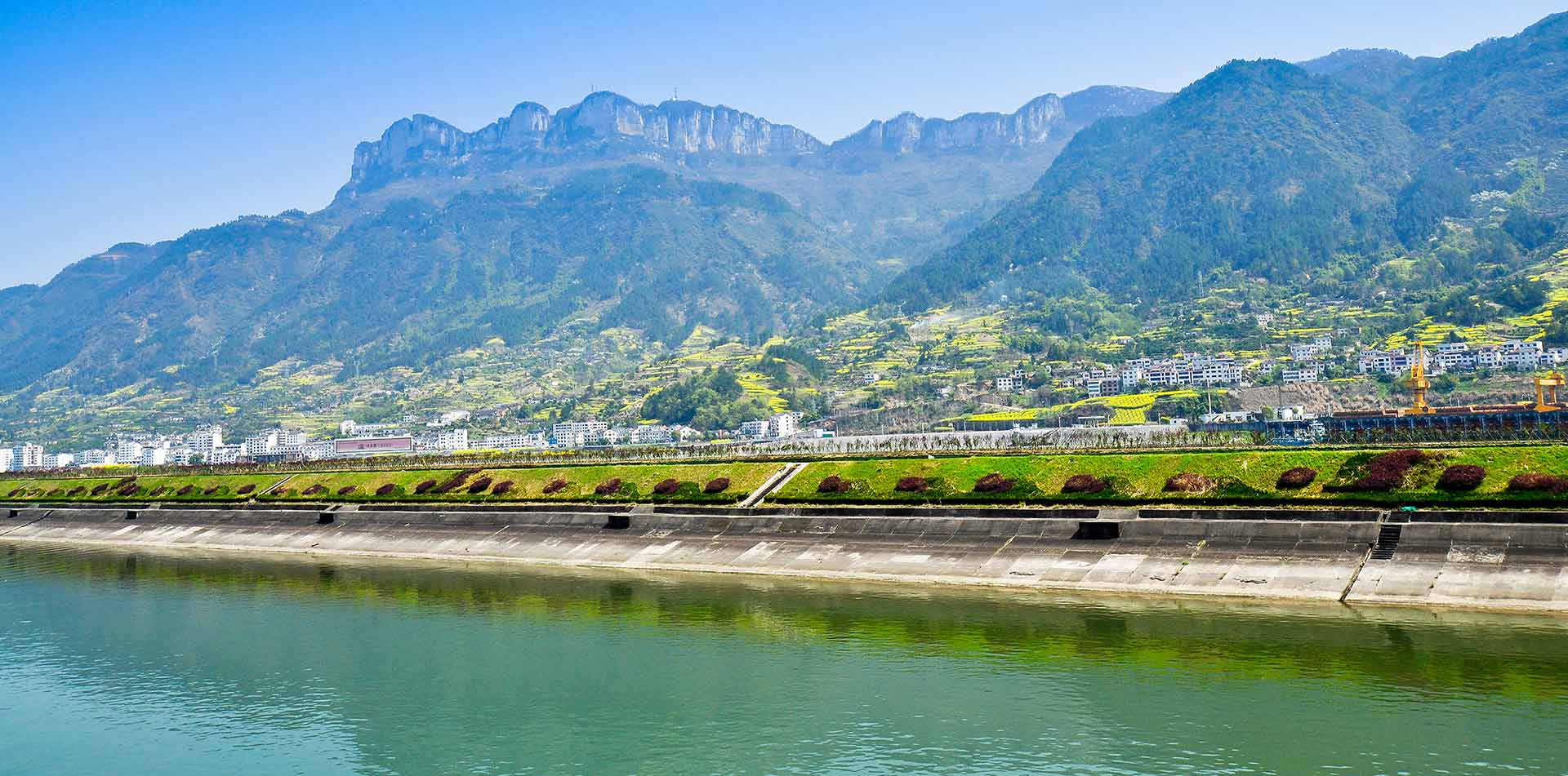 Asia China shoreline along the Yangtze River with village and mountains - luxury vacation destinations