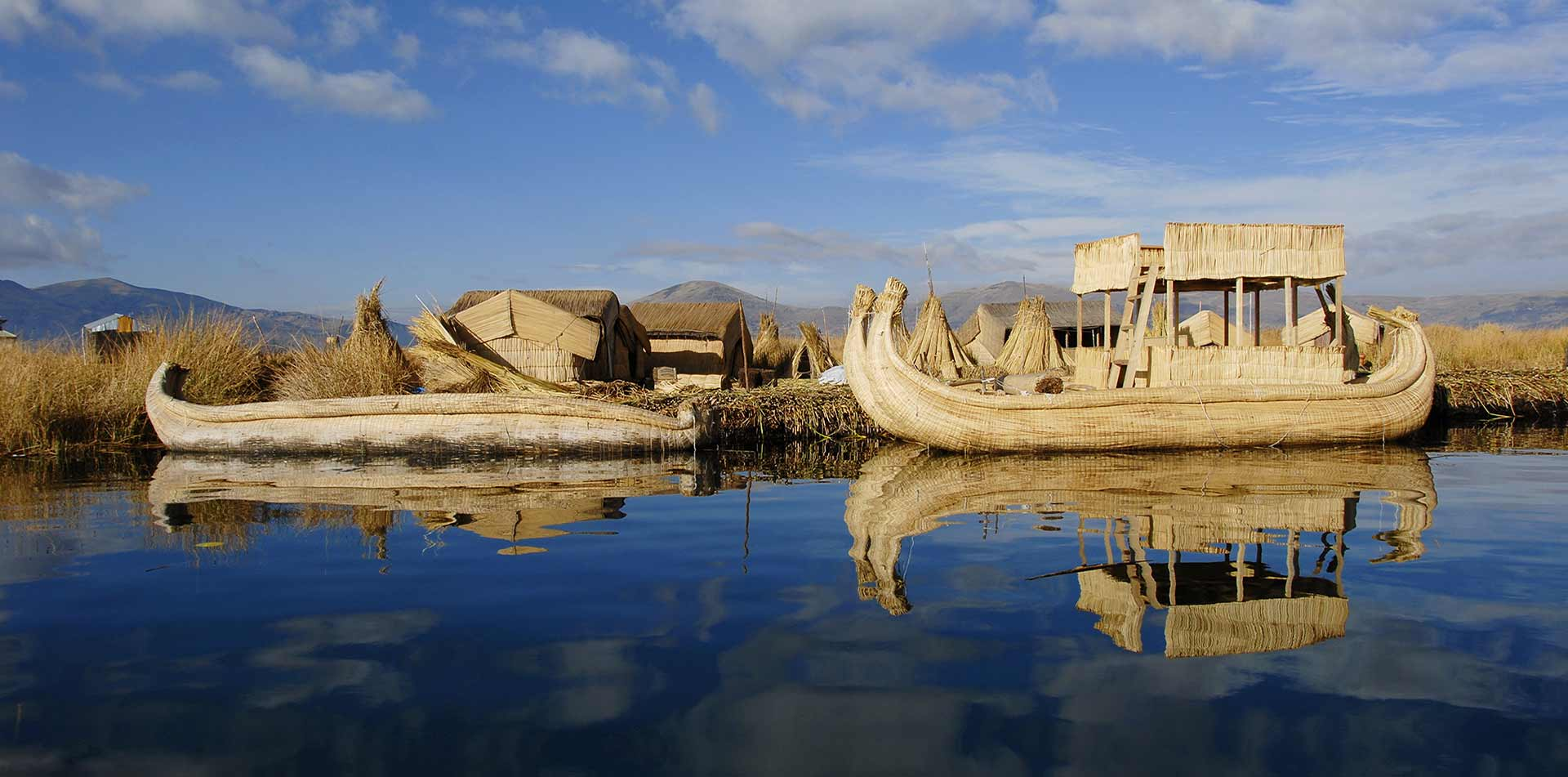 South America Peru Lake Titicaca floating island handmade totora reeds boat local Uros village - luxury vacation destinations