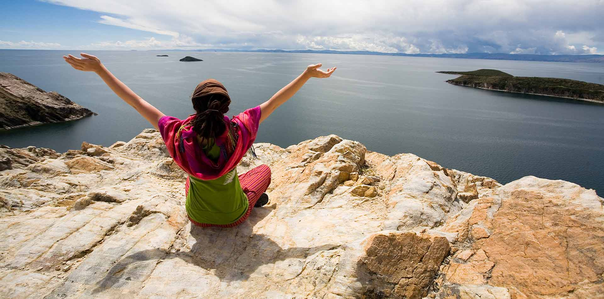 South America Peru Lake Titicaca woman sitting with arms raised looking at scenic view - luxury vacation destinations