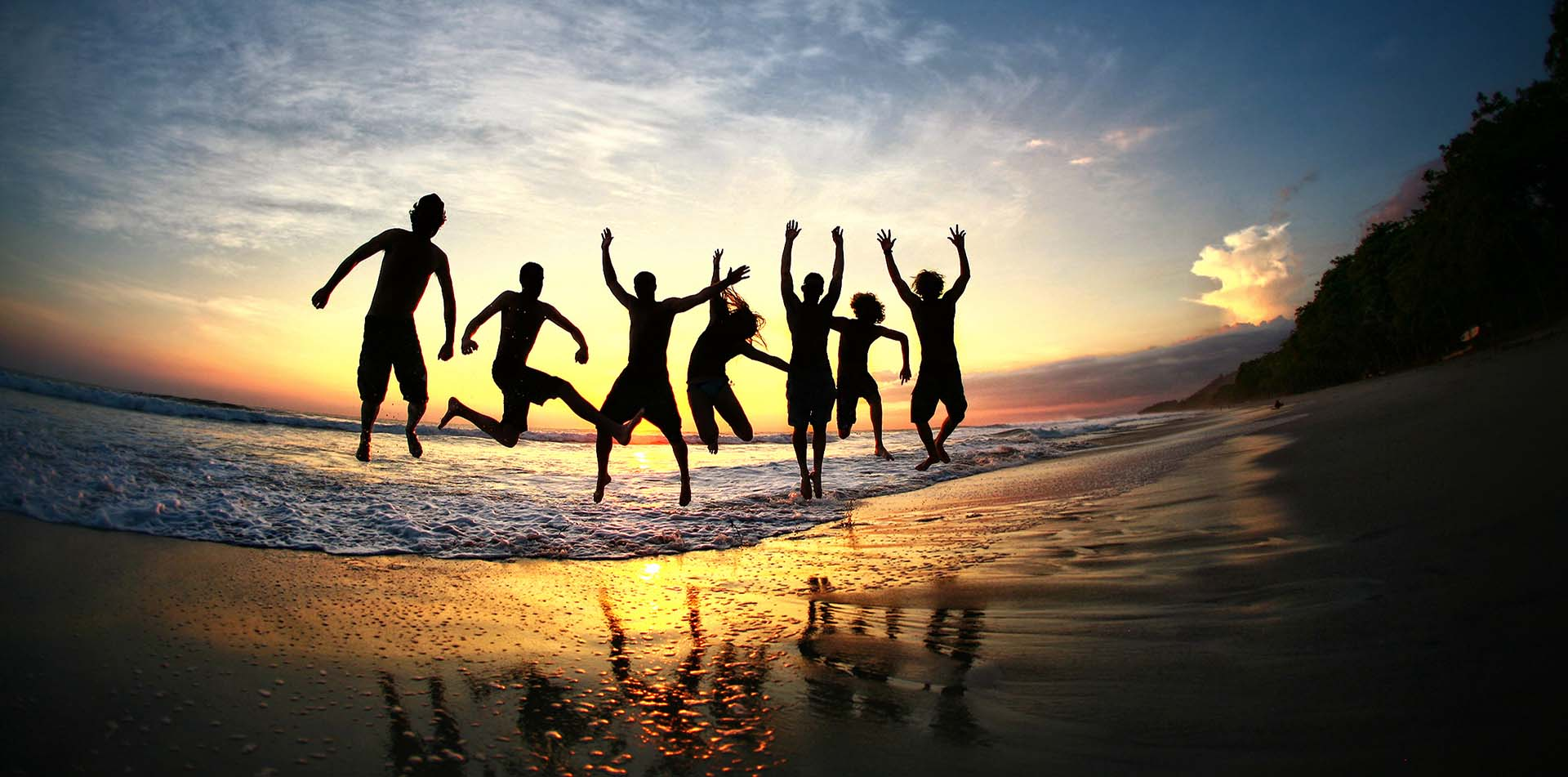 Friends Jumping on Beach at Sunset, Costa Rica