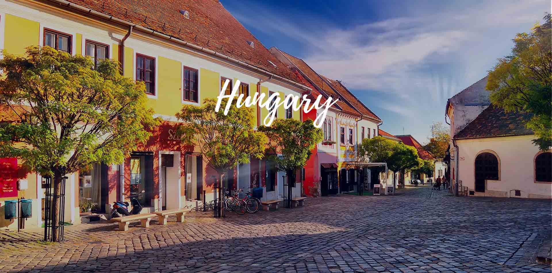 Europe Hungary Budapest cobblestone city street with colorful storefronts - luxury vacation destinations
