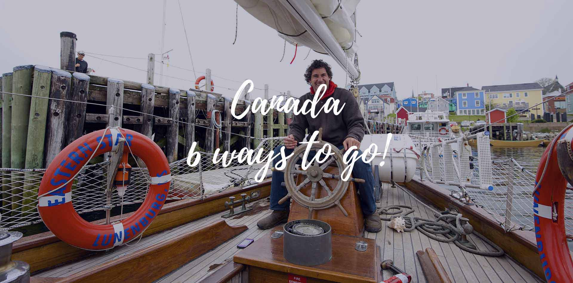 North America Canada 6 ways to go Nova Scotia Lunenberg wood sailboat man smiling steering - luxury vacation destinations