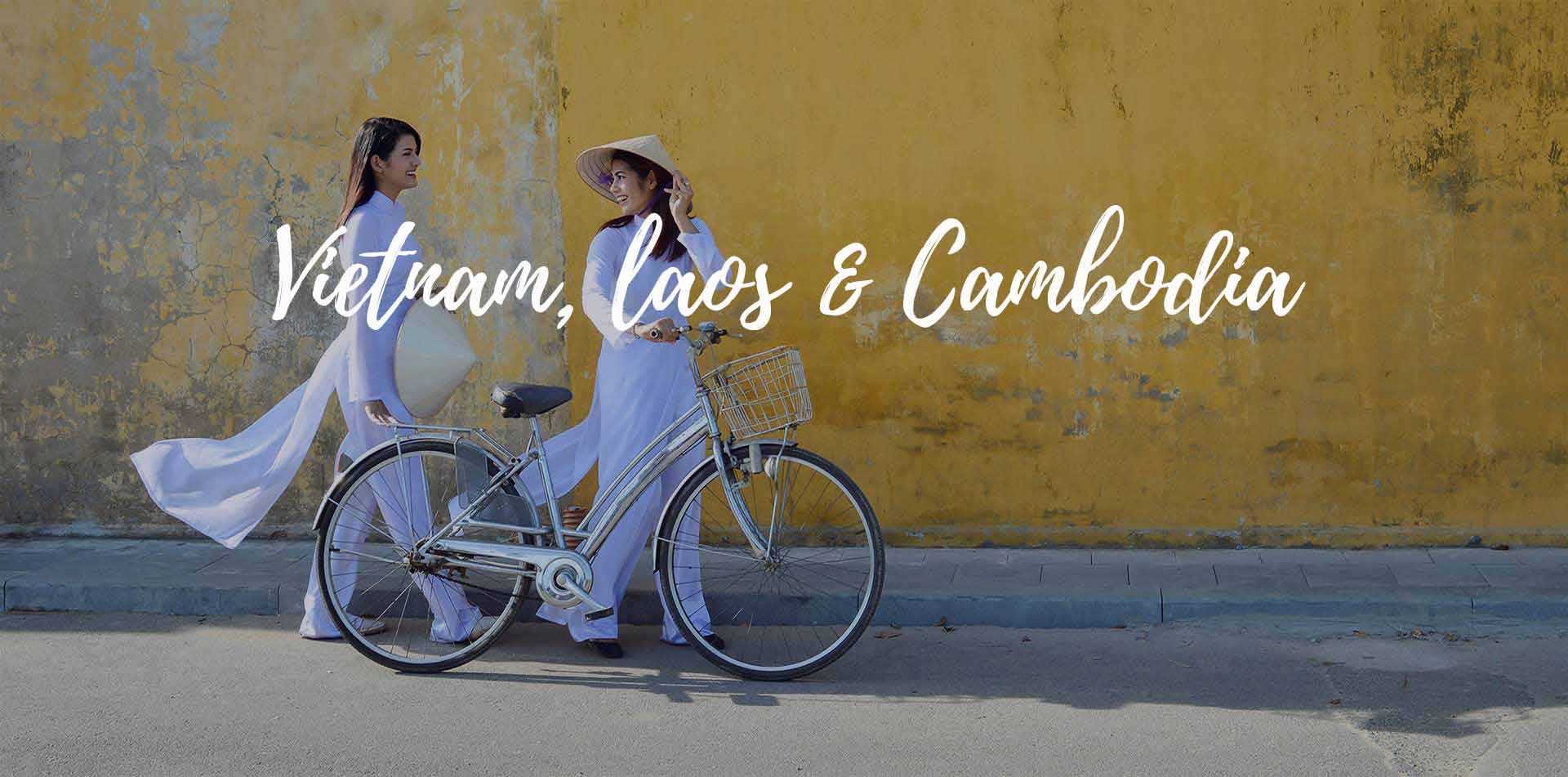 Asia Vietnam Laos and Cambodia local women wearing white walking with a bike on Hoi An street - luxury vacation destinations