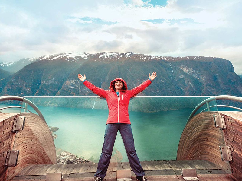 Europe woman leaning on glass smiling arms raised scenic snow-capped mountains beautiful water - luxury vacation destinations