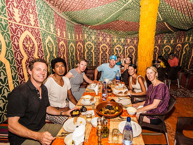 Africa Morocco Sahara Desert colorful nomadic Berber encampment group smiling eating dinner - luxury vacation destinations