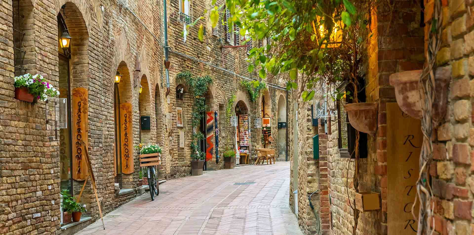 Europe Italy Tuscany Sienna local stone street in hillside town of San Gimignano - luxury vacation destinations