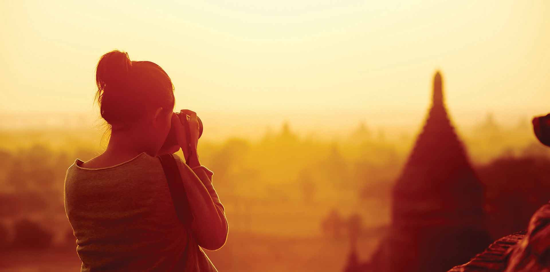 Woman taking photo of temple at sunset in Myanmar