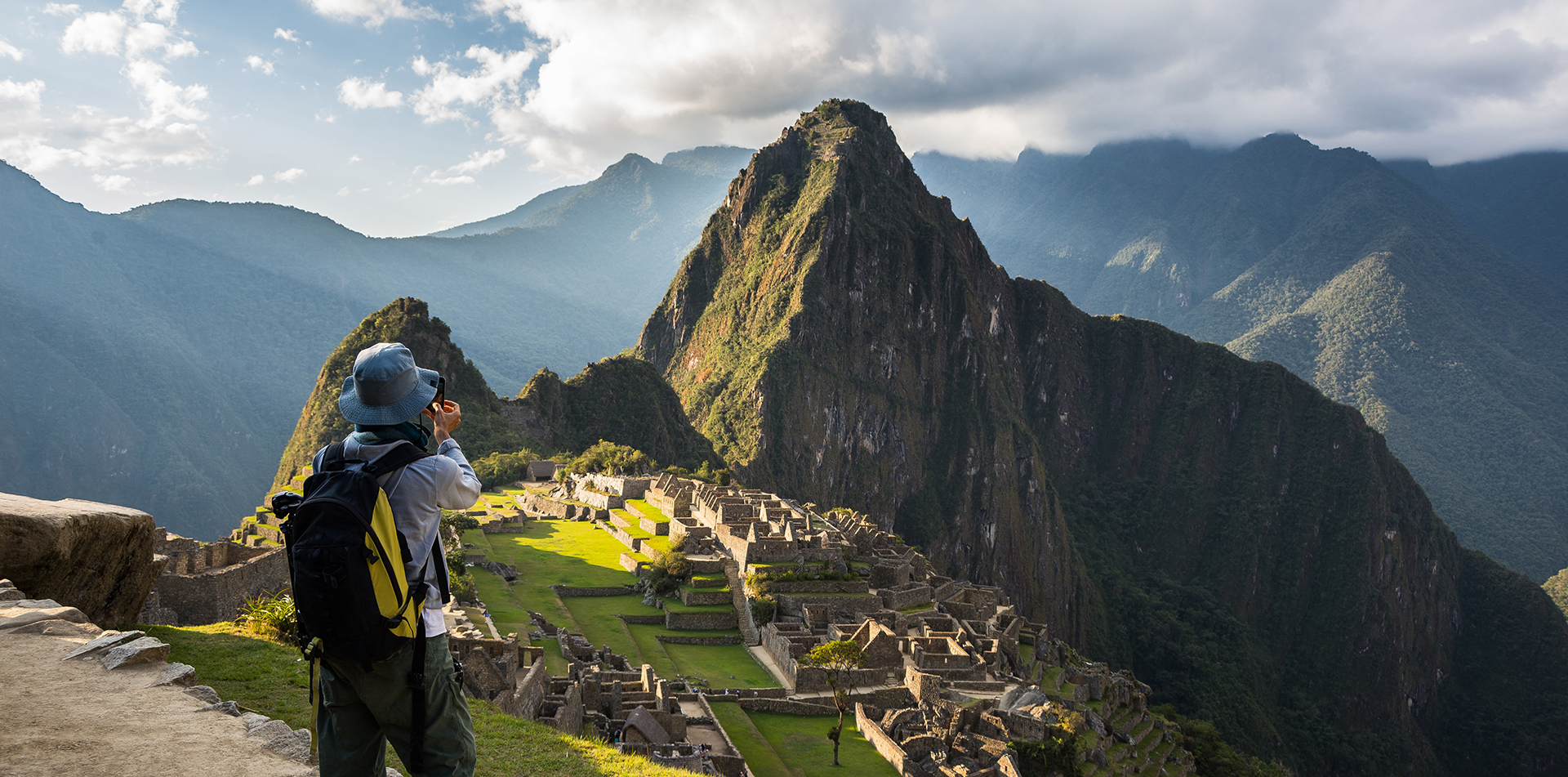 South America Peru Andes hiker taking photo of scenic Machu Picchu and ancient Inca ruins - luxury vacation destinations
