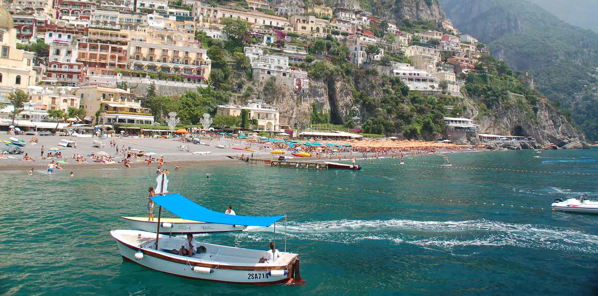 Europe Italy view of Cinque Terre beach and cliffside village from the water - luxury vacation destinations