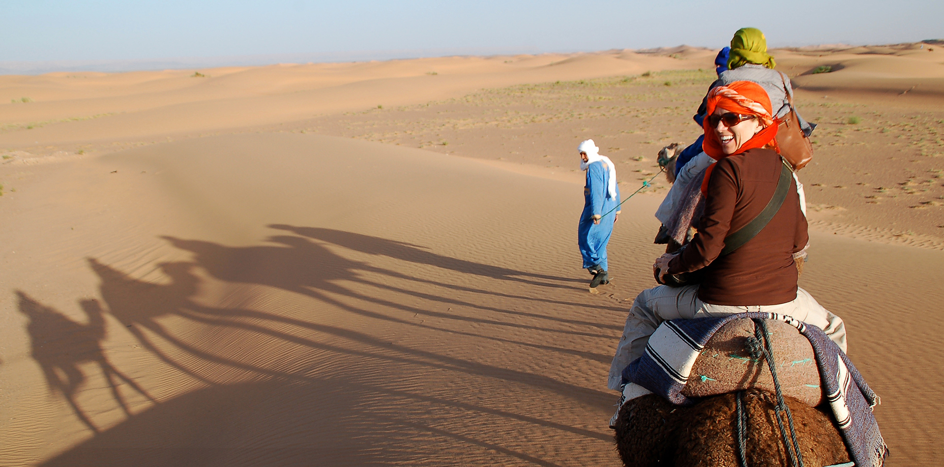 Africa Morocco Sahara Desert woman laughing riding camel caravan tribal Blue Man sand dunes - luxury vacation destinations