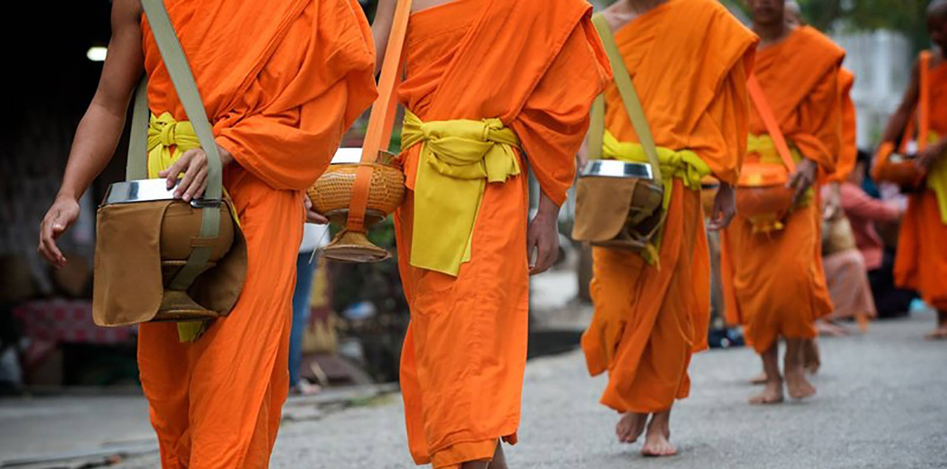 Asia Laos Luang Prabang Buddhist monks in orange participating in alms giving ceremony - luxury vacation destinations