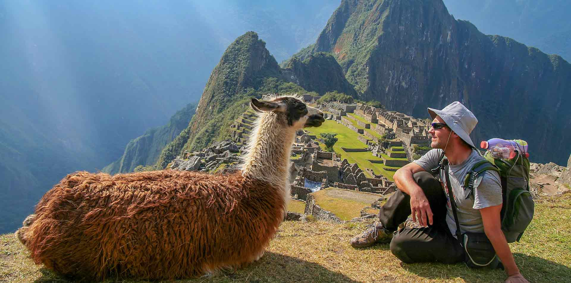 South America Peru Machu Picchu man and llama sitting staring in front of ancient Inca ruins - luxury vacation destinations