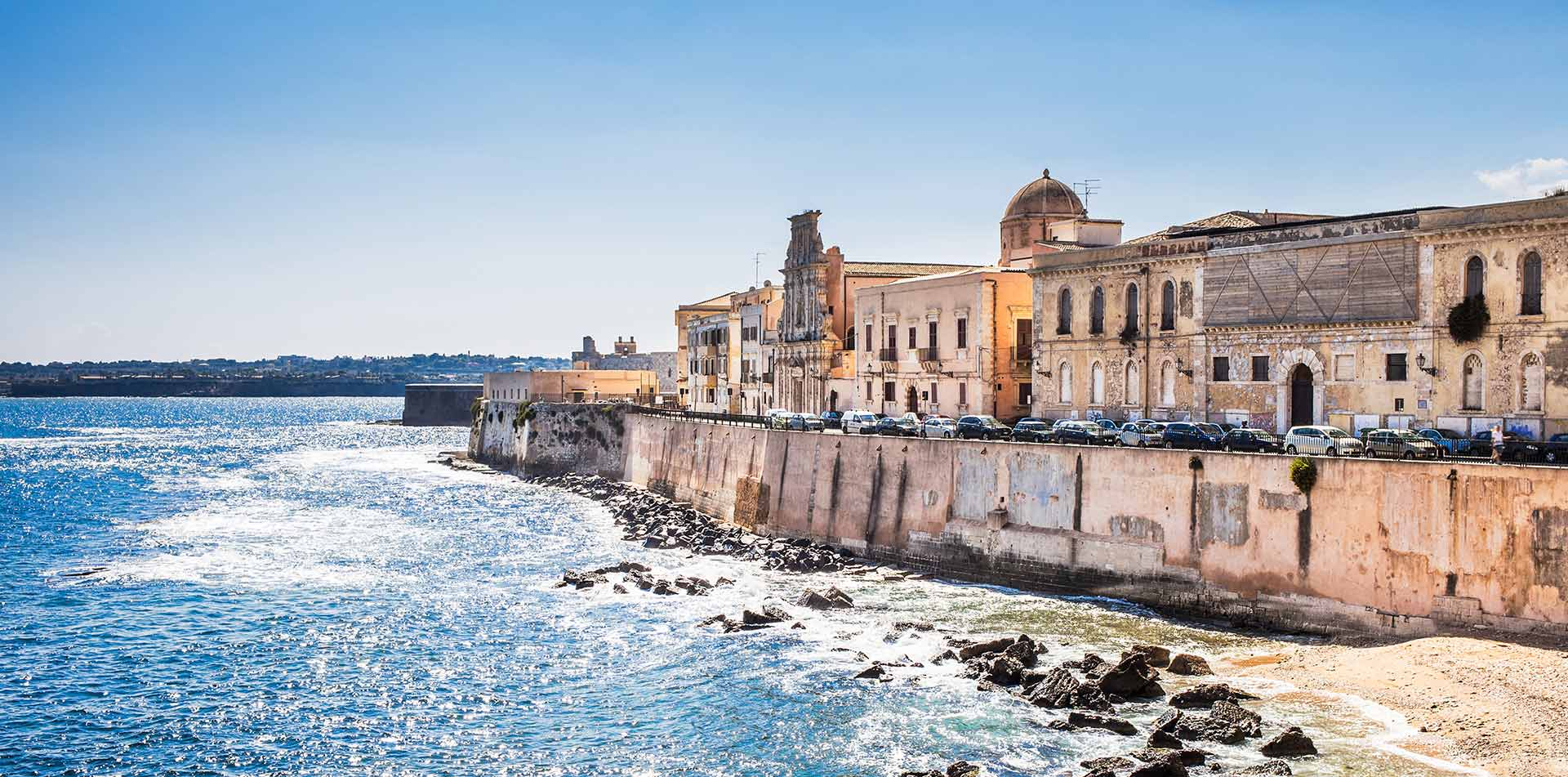 Europe Italy Sicily Siracusa old buildings along coastal sea wall at daytime - luxury vacation destinations