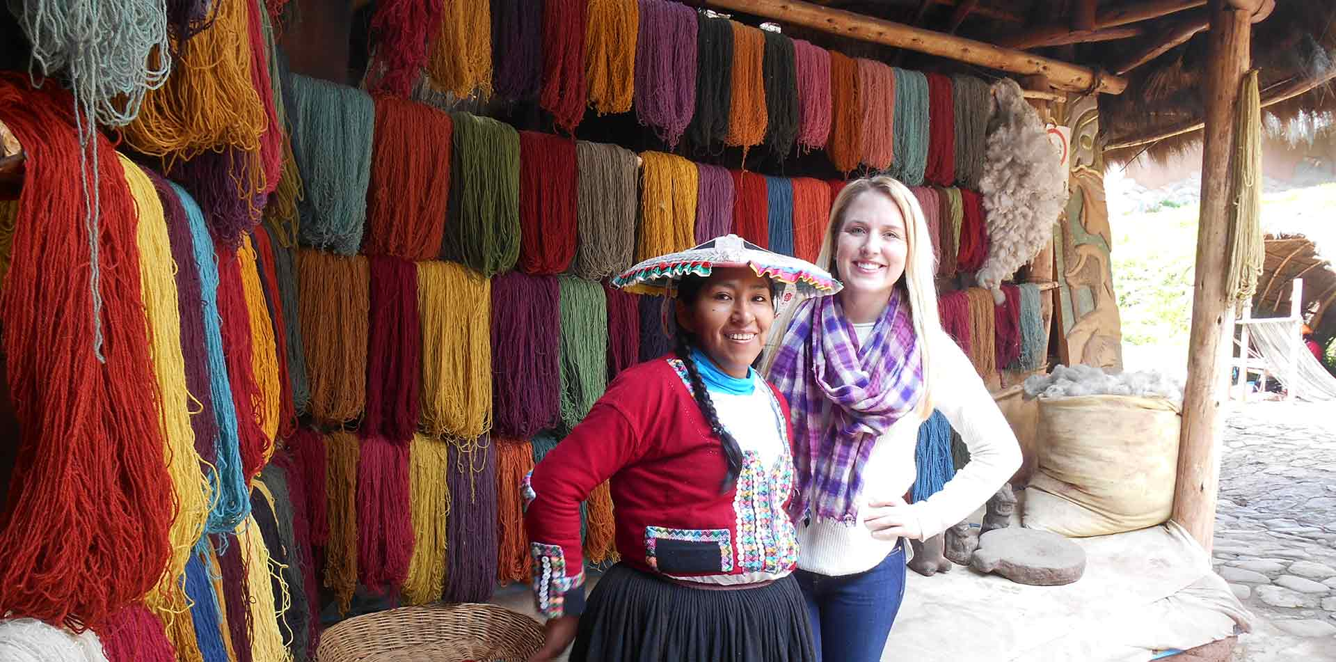 South America Peru Quechua local and young woman smiling posing in front of colorful yarn - luxury vacation destinations