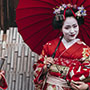 Asia Japan traditional painted face geiko geisha wearing red carrying a parasol - luxury vacation destinations