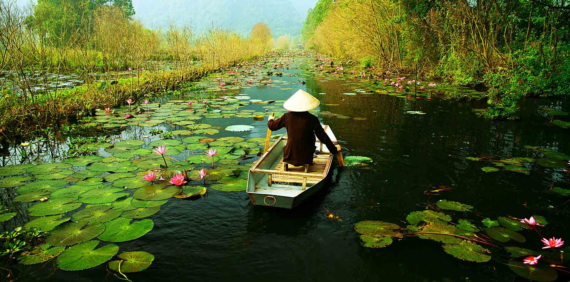 Asia Vietnam local in paddy hat rowing a boat down a river near the Mekong Delta - luxury vacation destinations
