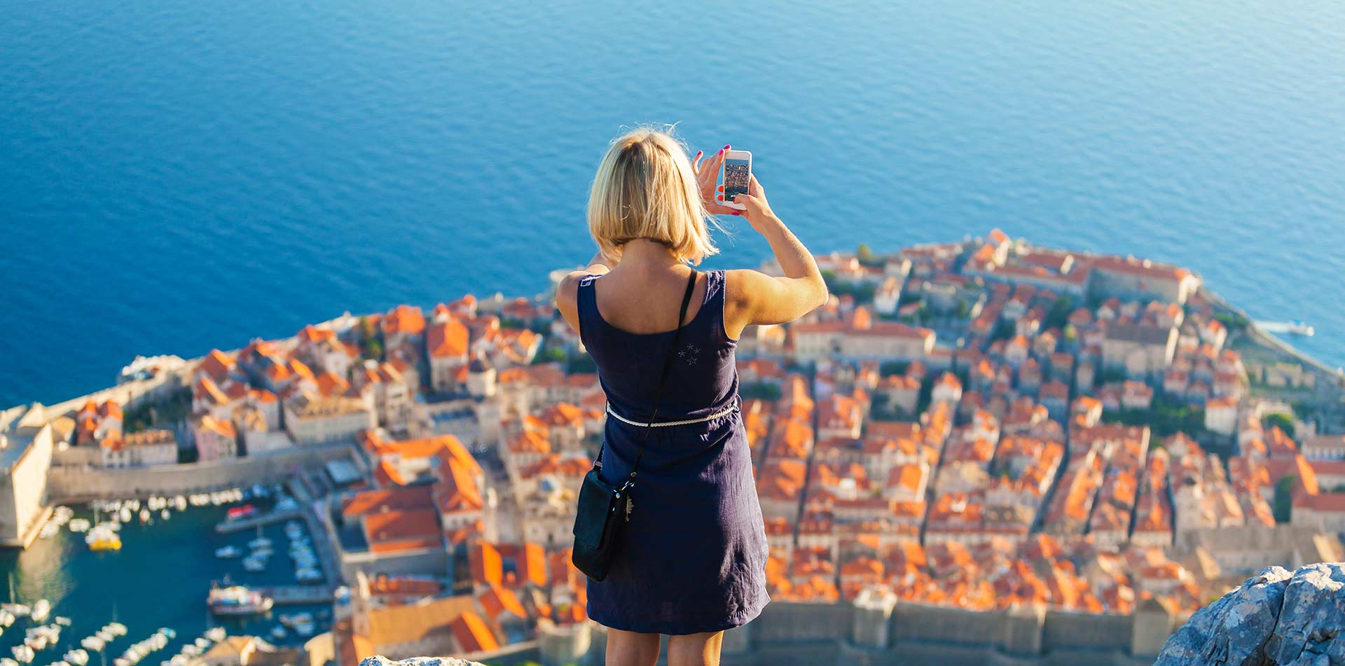 Europe Croatia Dubrovnik woman taking photo scenic Adriatic historic old town red tile roofs - luxury vacation destinations