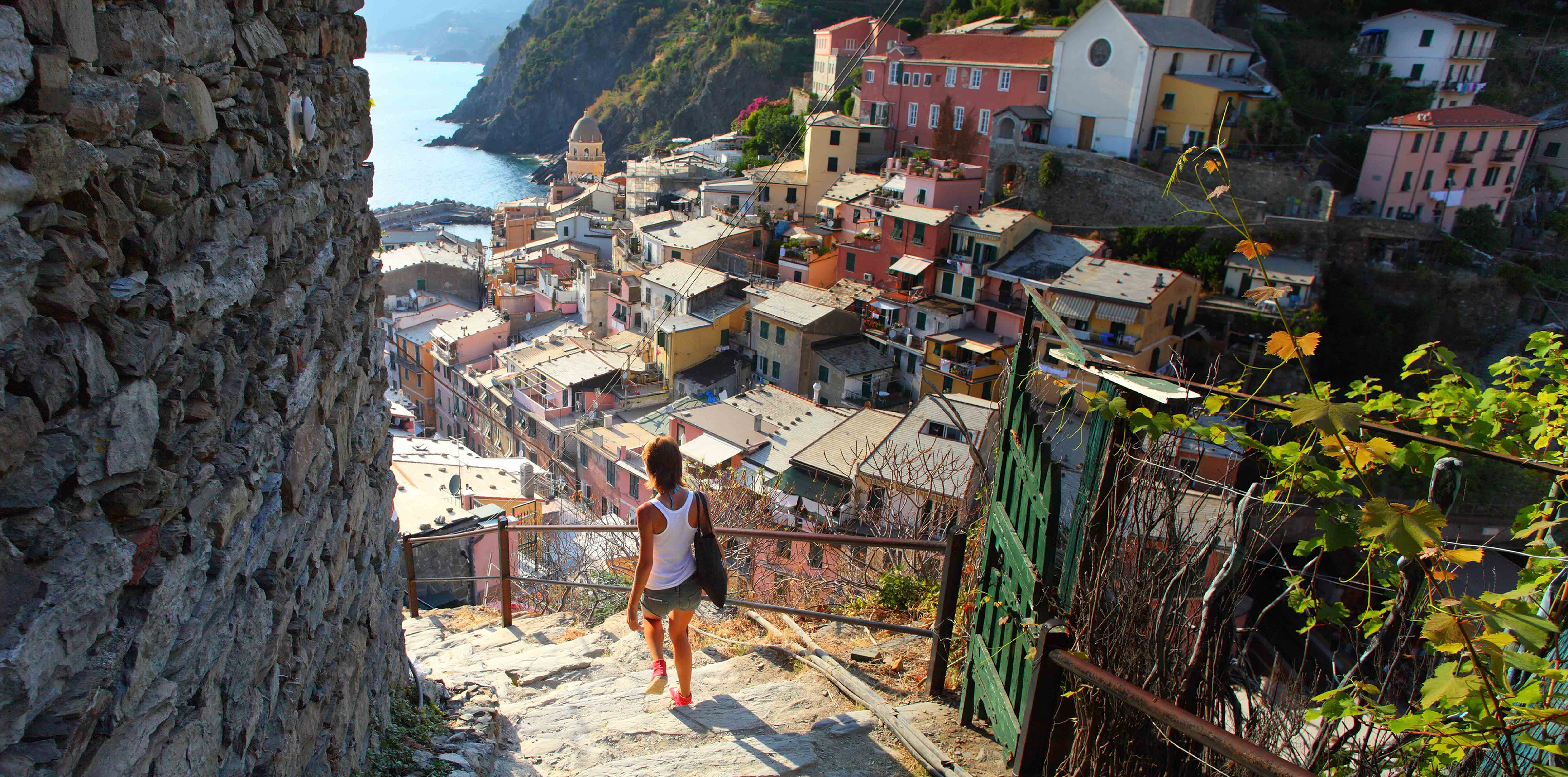 Europe Italy woman exploring colorful homes and beautiful views of the coastline-luxury vacation destinations