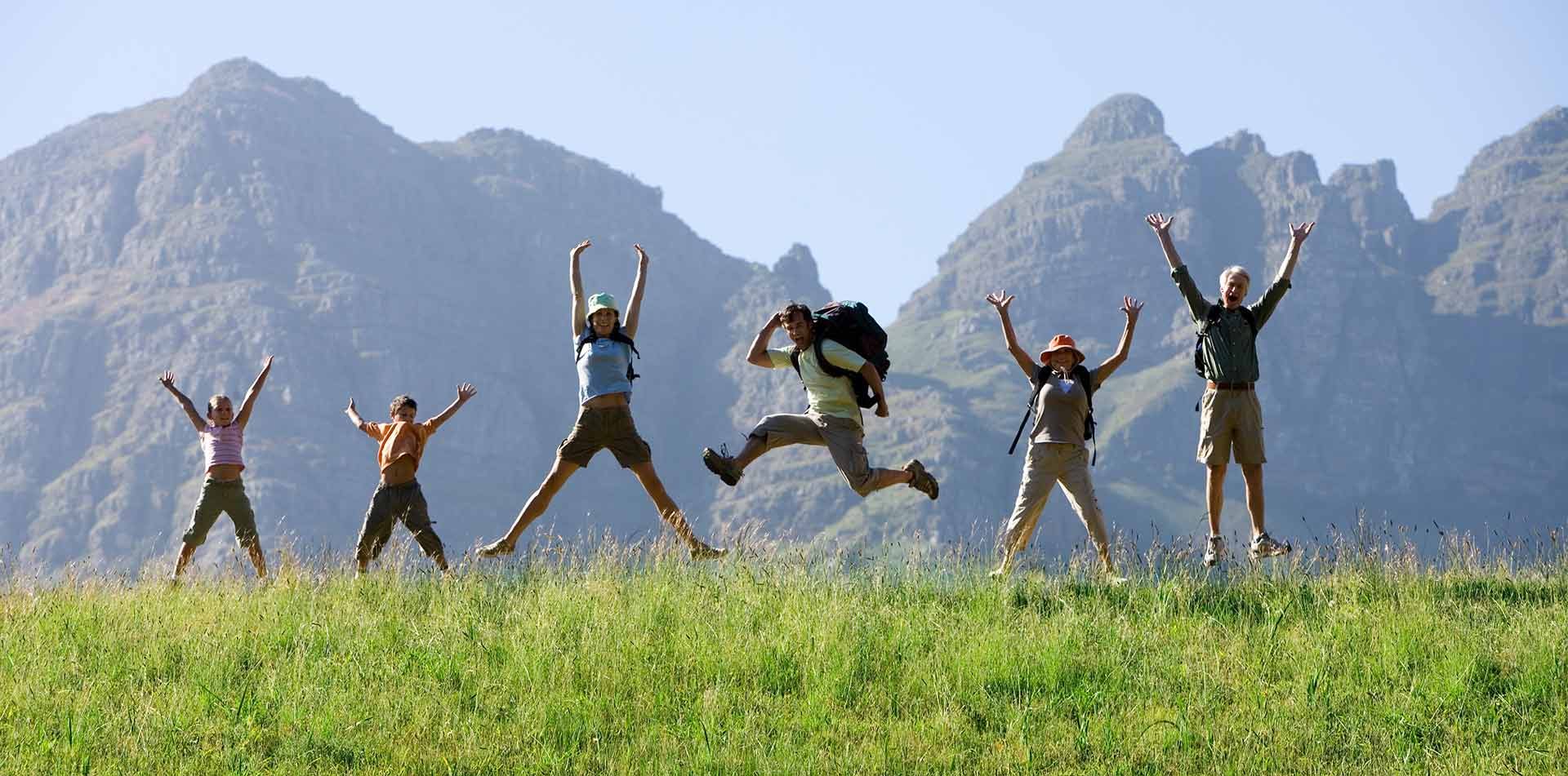 Family jumping in field, Family Journeys