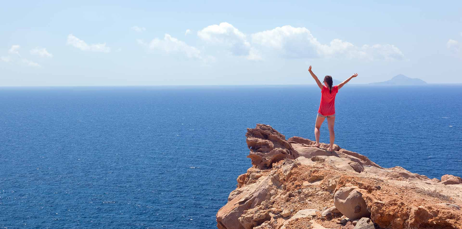 Woman with arms out on cliff, Greece