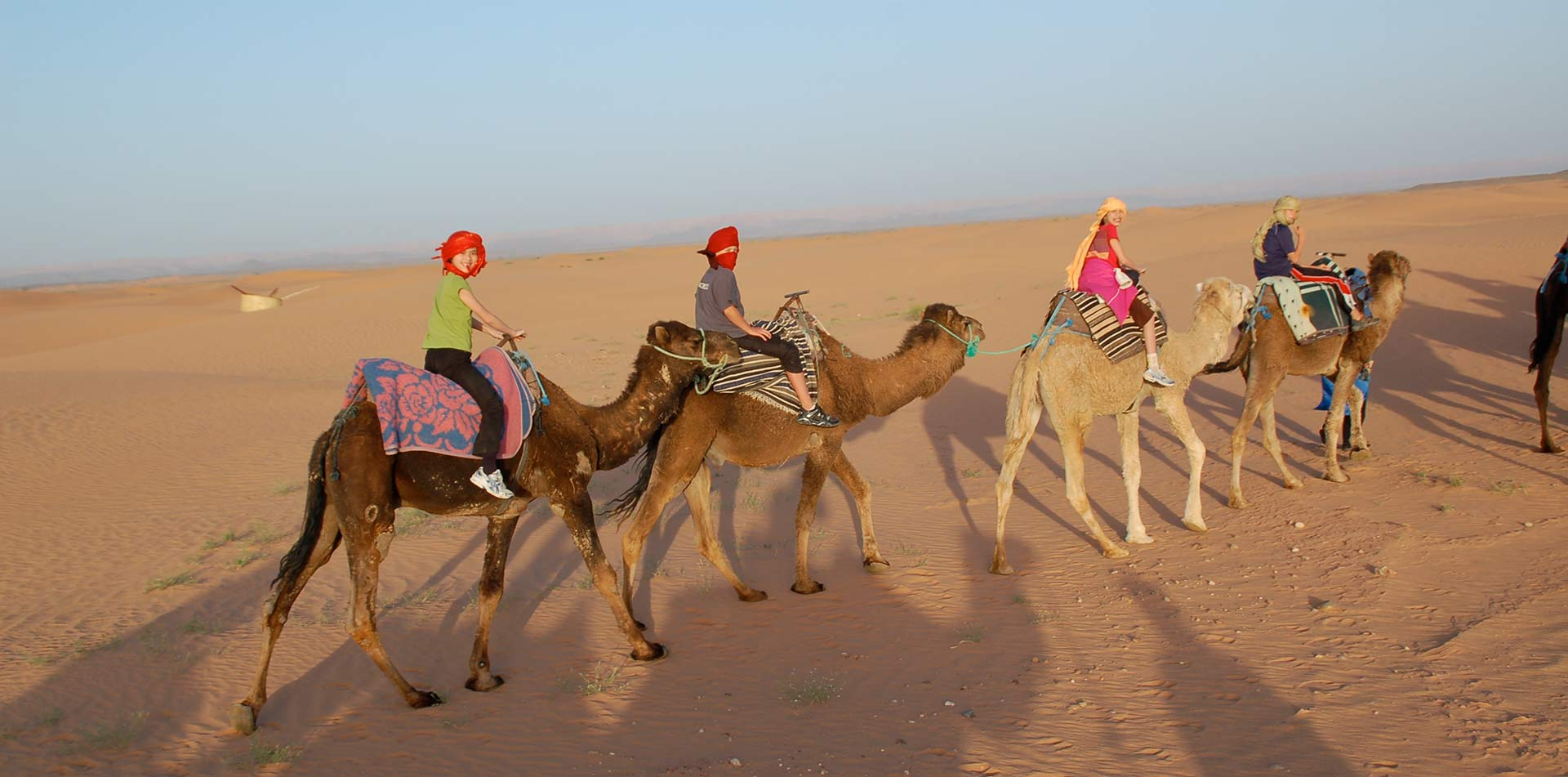 Kids riding camels in Morocco