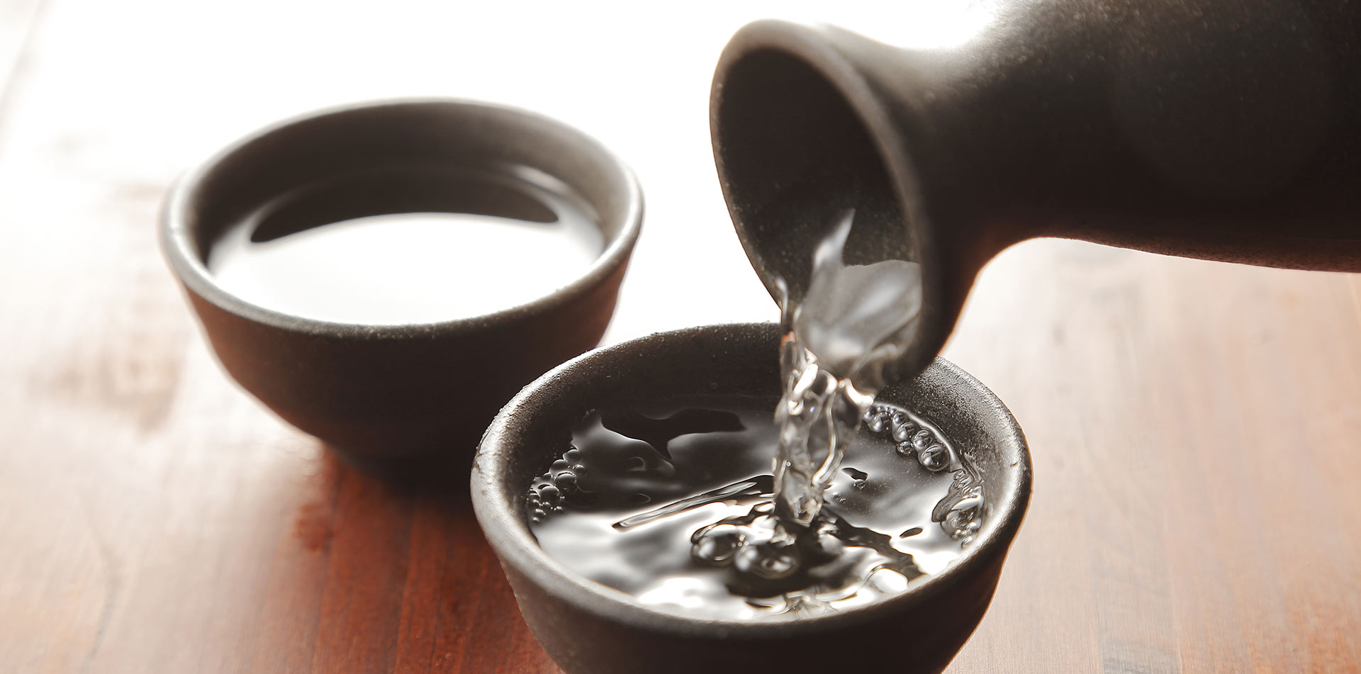 Asia Japan sake being poured into earthenware cups - luxury vacation destinations