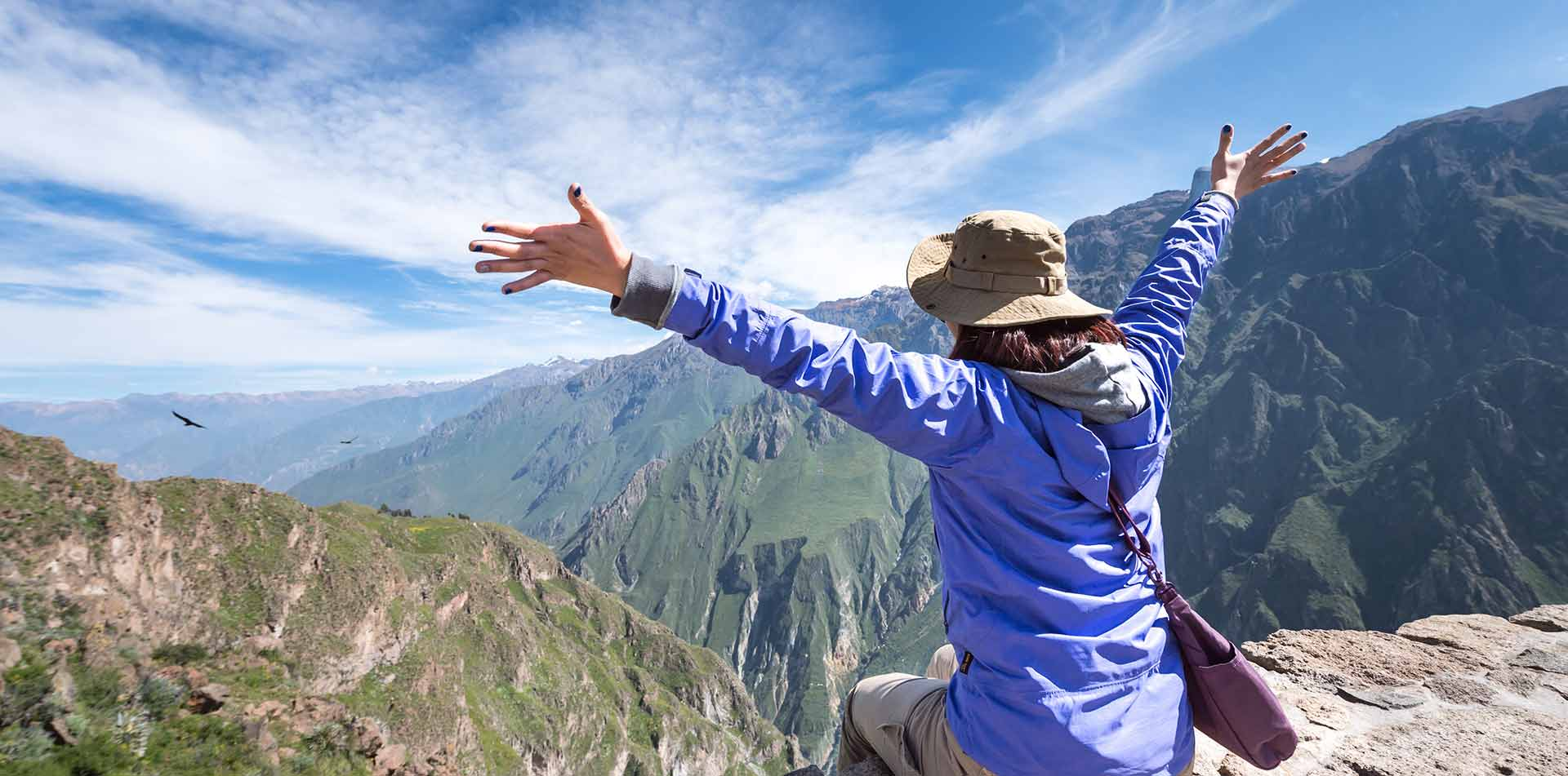 Woman with arms out looking at mountains