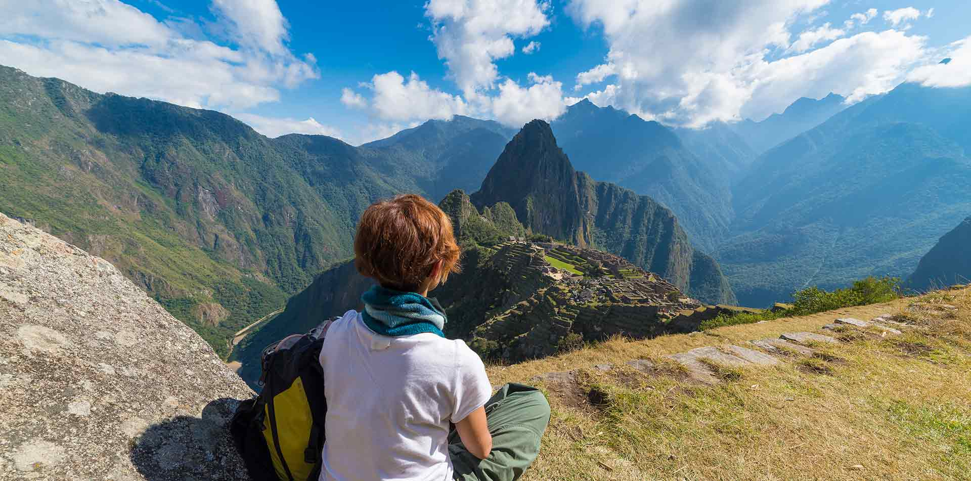 South America Peru Andes woman sitting looking at scenic Machu Picchu and ancient Inca ruins - luxury vacation destinations