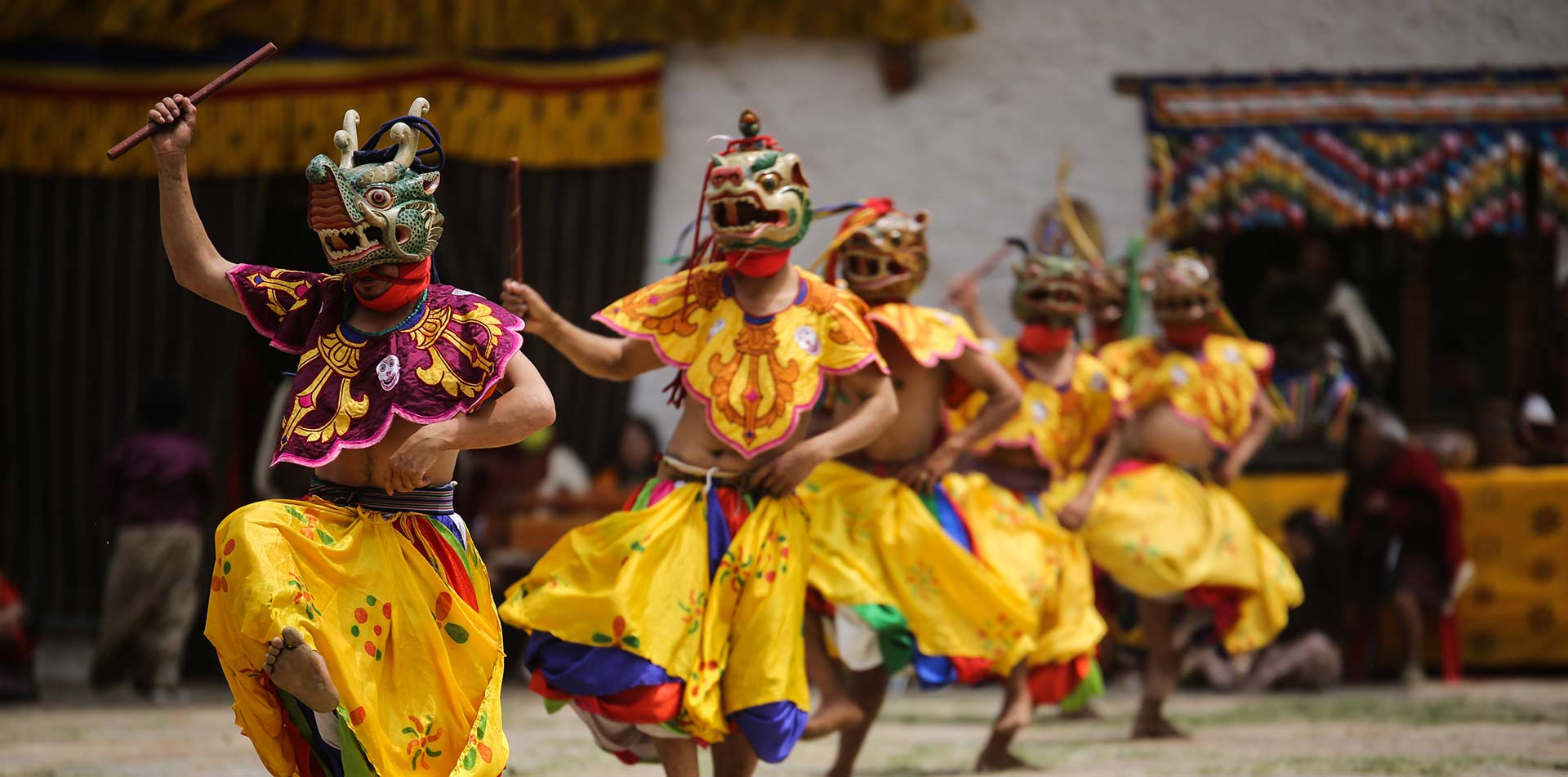 Asia Bhutan local dancers wearing traditional clothing and masks - luxury vacation destinations