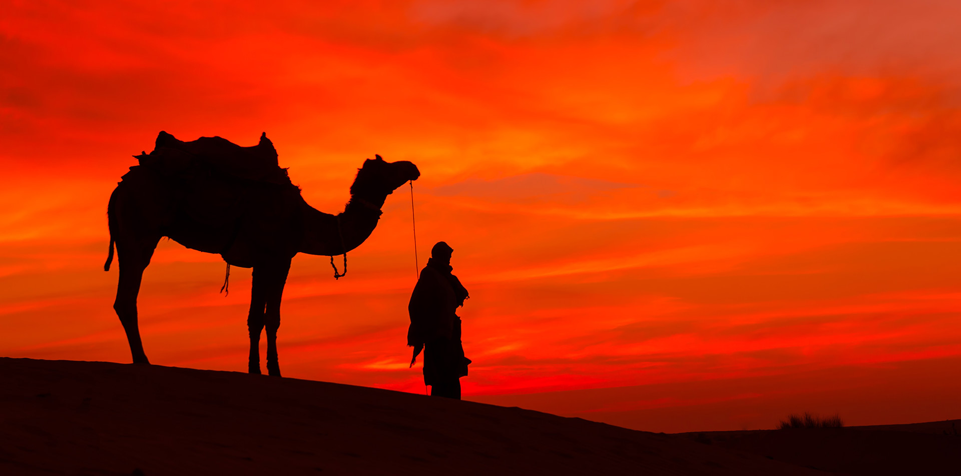 Africa Morocco Sahara Desert silhouette of camel and tribesman beautiful red and orange sunset - luxury vacation destinations