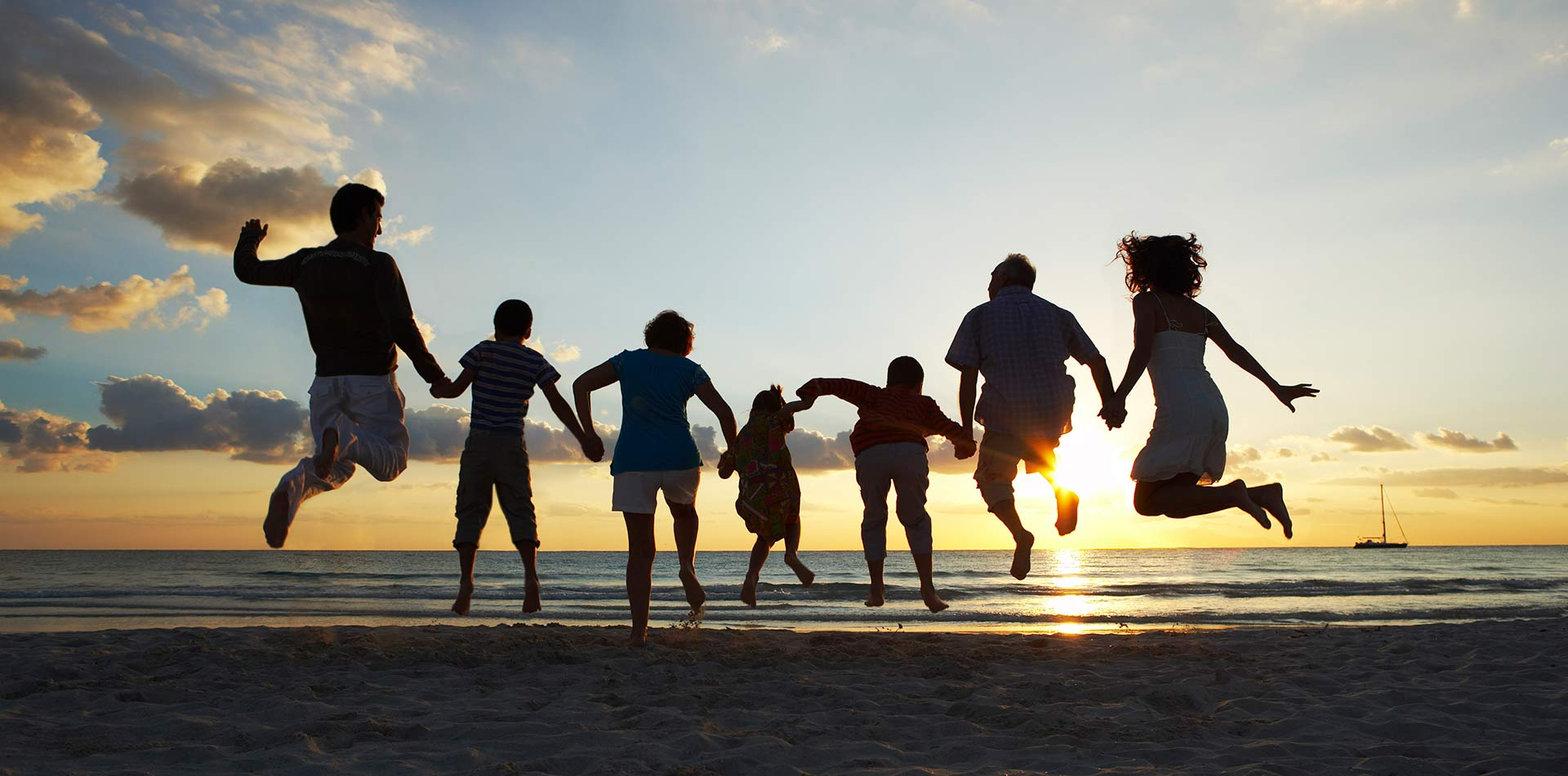 Family jumping on the beach at sunset - luxury vacation destinations