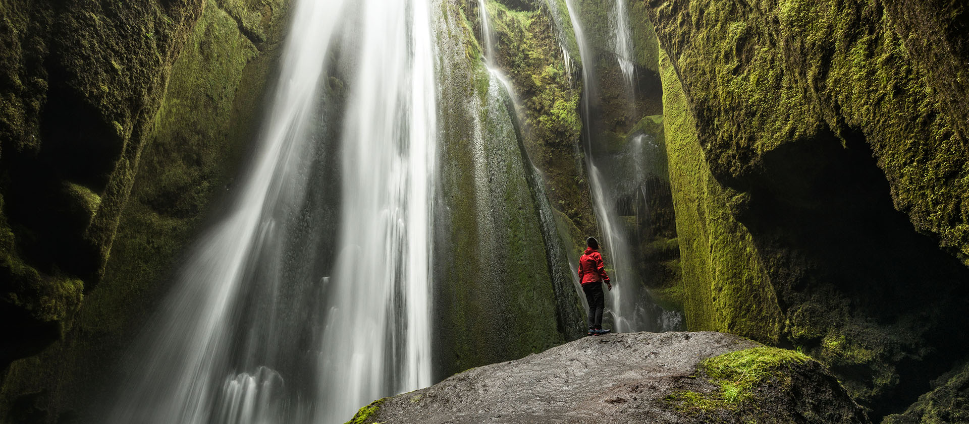 Europe Iceland woman in red jacket standing on rock in waterfall cave - luxury vacation destinations