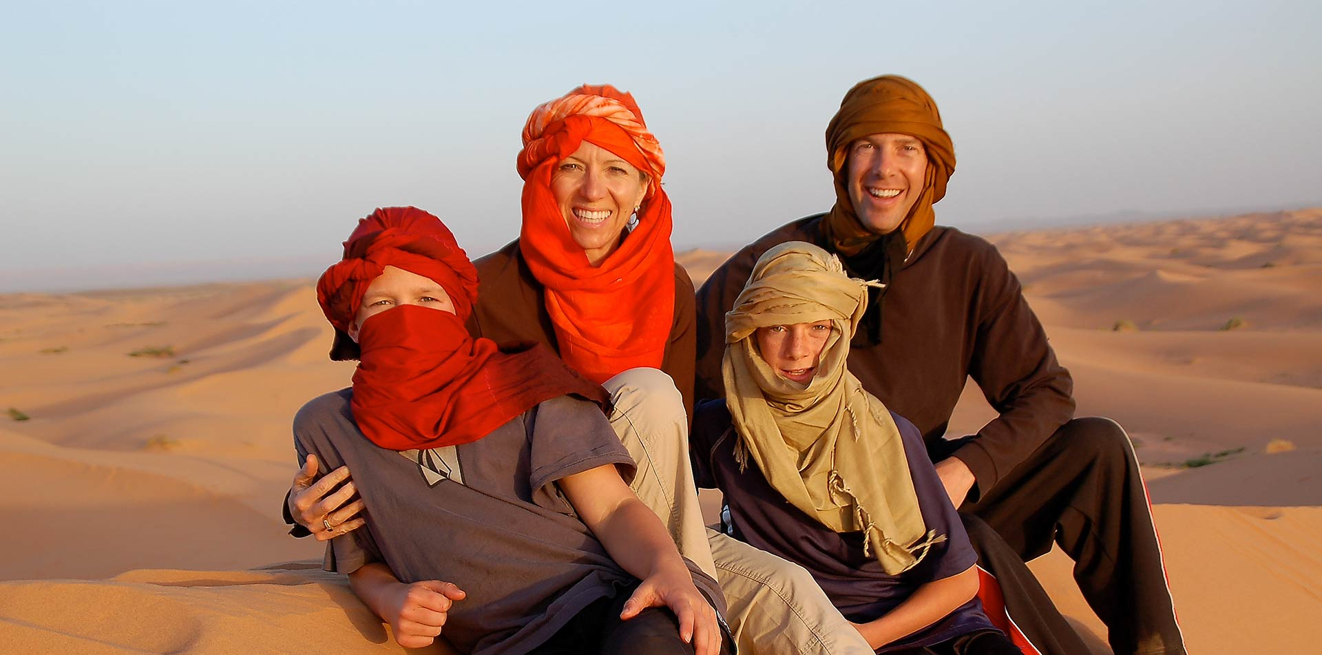 Africa Morocco Sahara Desert happy family wearing colorful head scarves smiling tan sand dunes - luxury vacation destinations
