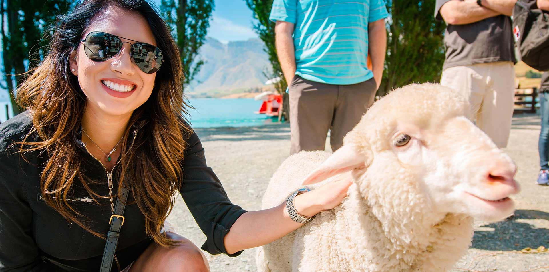 Oceania New Zealand Queenstown woman petting sheep at Mt. Nicholas Farm - luxury vacation destinations