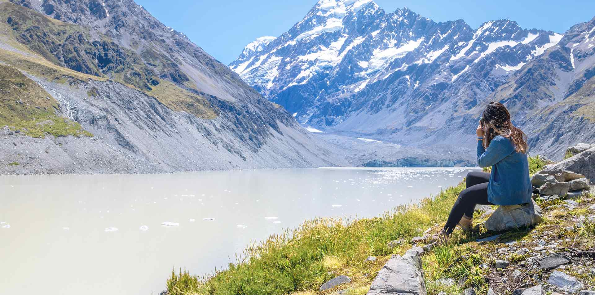 Oceania New Zealand Aoraki Mount Cook National Park woman sitting near Hooker Glacier - luxury vacation destinations