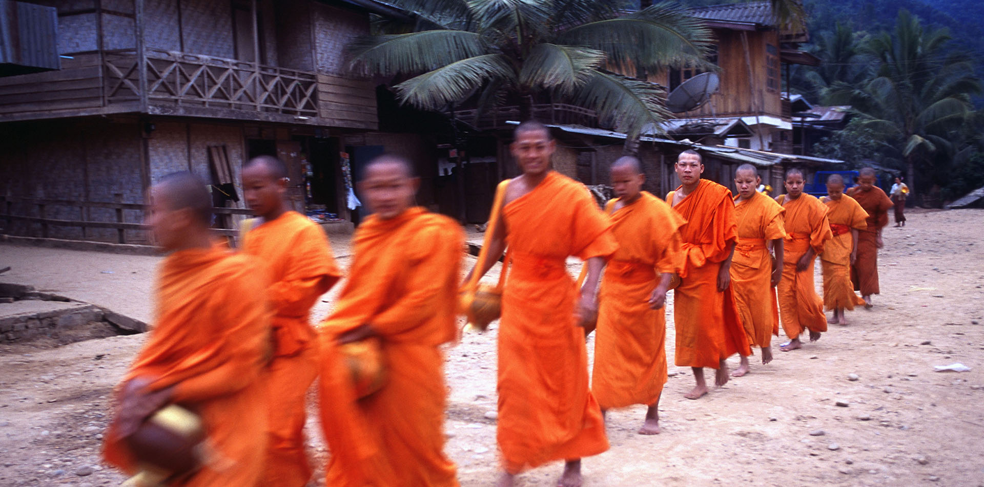 Asia Laos Luang Prabang Buddhist monks in orange participating during alms giving ceremony - luxury vacation destinations