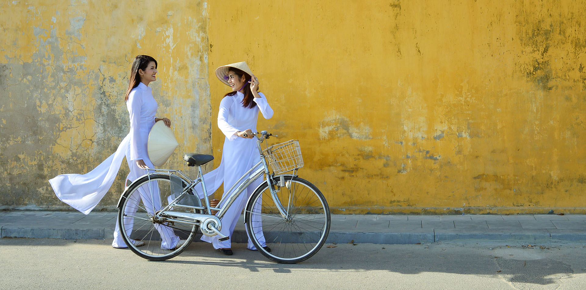 Asia Vietnam local women wearing white walking with a bike on Hoi An street - luxury vacation destinations