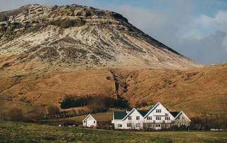 Europe Iceland Hvolsvollur Skalakot Manor Hotel local family-run farm with mountains in back - luxury vacation destinations
