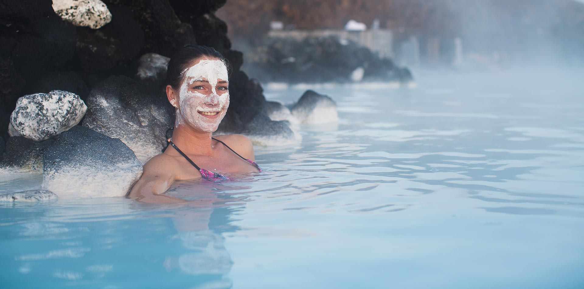Europe Iceland Blue Lagoon woman smiling with silica face mask relaxing in geothermal spa - luxury vacation destination