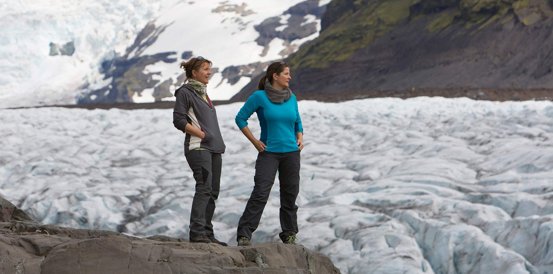 Europe Iceland tourist women standing near glacier ice flow overlooking icy landscape - luxury vacation destinations