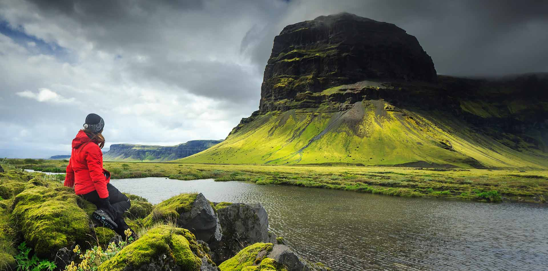 Europe Iceland woman sitting in front of lush green landscape with mountain cliff - luxury vacation destinations