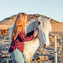 Europe Iceland girl petting white Icelandic horse on a local family farm - luxury vacation destinations
