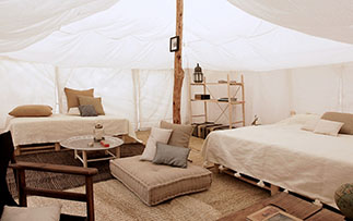 Africa Morocco Agafay Desert Scarabeo Camp bright white tent relaxing interior eclectic decor - luxury vacation destinations